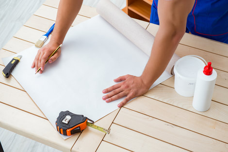 Painters and Decorators Swansea measuring and hanging wall paper